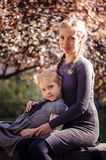 Mother with daughter in the autumn park. Mother with little daughter dressed in grey clothes walking in the autumn park Stock Images