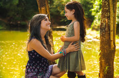 Mother with little daughter dressed in summerly dresses posing happily embracing for camera, outdoor small forest lake Royalty Free Stock Photos