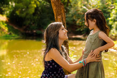 Mother with little daughter dressed in summerly dresses posing happily embracing for camera, outdoor small forest lake Stock Photos