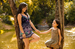 Mother with little daughter dressed in summerly dresses posing happily holding hands for camera, outdoor small forest Stock Image