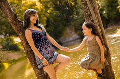 Mother with little daughter dressed in summerly dresses posing happily holding hands for camera, outdoor small forest Royalty Free Stock Images