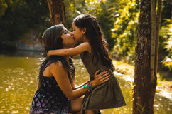 Mother with little daughter dressed in summerly dresses posing happily kissing for camera, outdoor small forest lake Stock Image