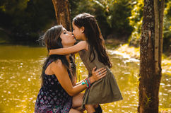 Mother with little daughter dressed in summerly dresses posing happily kissing for camera, outdoor small forest lake Royalty Free Stock Image