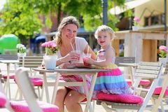 Mother and little daughter drinking in cafe Stock Photography