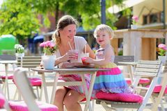 Mother and little daughter drinking in cafe Royalty Free Stock Photo