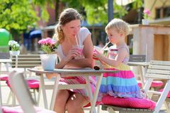 Mother and little daughter drinking in cafe Stock Image