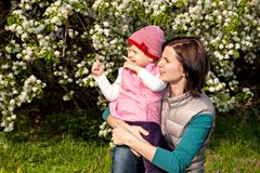 Mother and little daughter at flowers background Royalty Free Stock Image