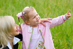 Mother and little daughter on green summer meadow Royalty Free Stock Images