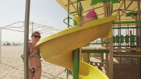 Mother and little daughter have fun at playground at sea beach in sunny day. UHD, 4k stock video