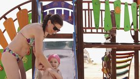 Mother and little daughter have fun at playground at sea beach in sunny day stock video