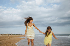 Mother and little daughter are having fun on the beach. Happiness and enjoyment Stock Photos