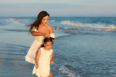 Mother and little daughter are having fun on the beach. Happiness and enjoyment Royalty Free Stock Photography