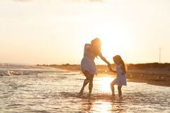 Mother and little daughter are having fun on the beach. Portrait of mother and little daughter are having fun on the beach. Happiness and enjoyment Royalty Free Stock Images