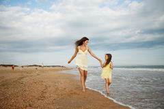 Mother and little daughter are having fun on the beach. Portrait of mother and little daughter are having fun on the beach. Happiness and enjoyment Royalty Free Stock Image