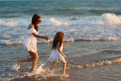 Mother and little daughter are having fun on the beach Royalty Free Stock Photo