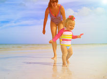 Mother and little daughter having fun on the beach Stock Images