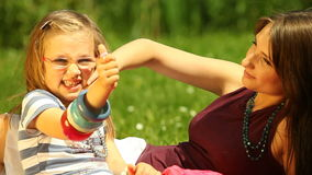 Mother with little daughter having fun on the meadow Royalty Free Stock Images