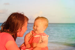 Mother and little daughter having fun at sunset beach Royalty Free Stock Images