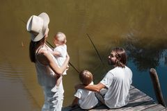 Mother with little daughter on her hands is looking how father and son fishing. All family dressed in the white clothes. royalty free stock photos