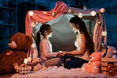Mother and daughter holding flashlight their hands in pillow house late at night at home. Royalty Free Stock Images