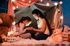 Mother and daughter holding flashlight their hands in pillow house late at night at home. Royalty Free Stock Photos