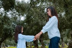 Mother and little daughter holding hands having fun in a park stock photography