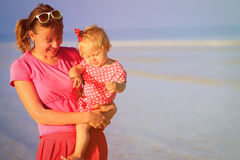 Mother and little daughter holding starfish at beach. Family vacation Stock Photography