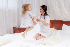 Mother and little daughter jumping on bed Stock Photo
