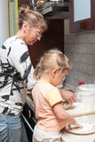 Mother and little daughter kneading dough together in kitchen Royalty Free Stock Photos