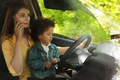 Mother with little daughter on knees driving car. Child in danger. Mother with little daughter on knees driving car and talking by phone. Child in danger stock image