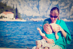 Mother and little daughter listening seashell at Royalty Free Stock Photos