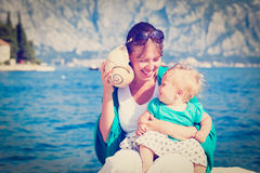 Mother and little daughter listening seashell Stock Photos