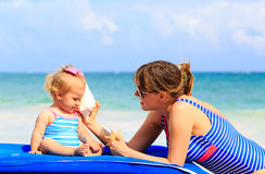 Mother and little daughter listening shells on the Royalty Free Stock Photos