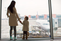 Mother and little daughter looking out the window at airport terminal Royalty Free Stock Image