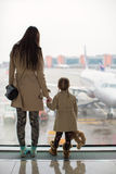Mother and little daughter looking out the window at airport terminal Stock Image