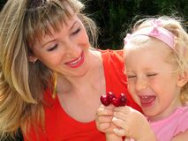 Mother with little daughter looks at cherry Stock Images