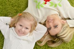 Mother with little daughter lying on green carpet Royalty Free Stock Images