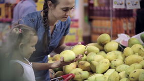 Mother with little daughter makes purchases in the supermarket. Family selecting fresh fruits