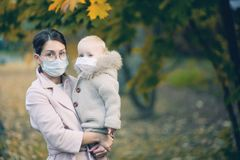 Mother and little daughter in medical masks in the autumn forest