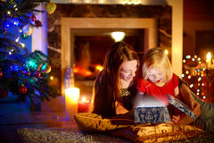 Mother and little daughter opening a magical Christmas gift. Young mother and her little daughter opening a magical Christmas gift by a Christmas tree in cozy Stock Photos