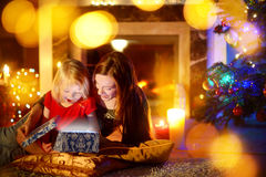 Mother and little daughter opening a magical Christmas gift Royalty Free Stock Image