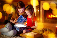 Mother and little daughter opening a magical Christmas gift. Young mother and her little daughter opening a magical Christmas gift by a Christmas tree in cozy Stock Photography