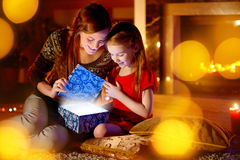 Mother and little daughter opening a magical Christmas gift. Young mother and her little daughter opening a magical Christmas gift by a Christmas tree in cozy Royalty Free Stock Images