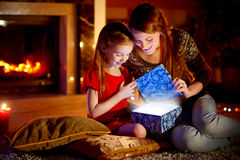 Mother and little daughter opening a magical Christmas gift. Young mother and her little daughter opening a magical Christmas gift by a Christmas tree in cozy Royalty Free Stock Image