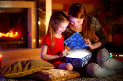 Mother and little daughter opening a magical Christmas gift. Young mother and her little daughter opening a magical Christmas gift by a Christmas tree in cozy Stock Photo