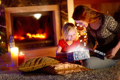 Mother and little daughter opening a magical Christmas gift. Young mother and her little daughter opening a magical Christmas gift by a Christmas tree in cozy Royalty Free Stock Photos