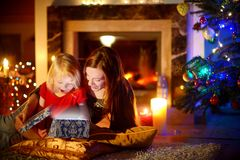 Mother and little daughter opening a magical Christmas gift. Young mother and her little daughter opening a magical Christmas gift by a Christmas tree in cozy Royalty Free Stock Photography