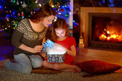 Mother and little daughter opening a magical Christmas gift. Young mother and her little daughter opening a magical Christmas gift by a Christmas tree in cozy Stock Images