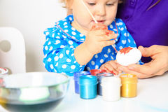 Mother and little daughter painting easter eggs Stock Images