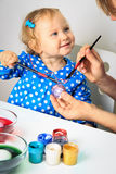Mother and little daughter painting easter eggs Stock Photo